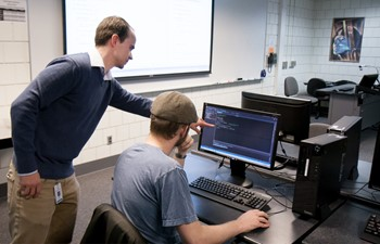 Teacher helping student at computer