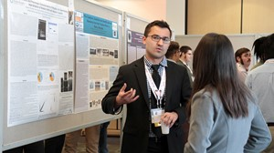 An Anoka-Ramsey Community College student discusses his undergraduate research as part of the college's Outstanding Scholarship, Creative Activities and Research Symposium (OSCARS).