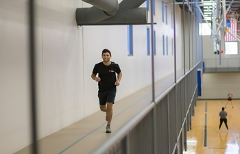 Student smiling and running along track