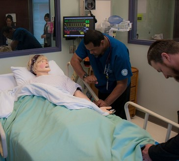 Nursing students checking vitals on practice dummy.