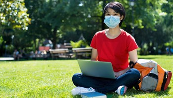 Student outside using laptop wearing face covering
