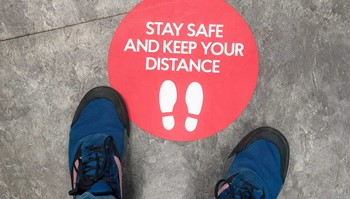 Shoes-near-keep-your-distance-sticker-on-ground