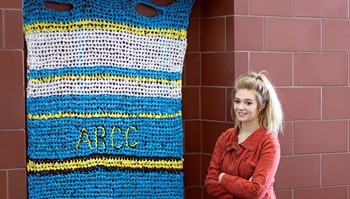 Anoka-Ramsey Community College President of the Student Sustainability Club, Paige Hanson (shown) stands by a mat the club produced for the organization Weaving for Love, which makes sleeping mats for the homeless. Collecting plastic bags for the mats is just one of the many activities the club does to promote environmental sustainability.