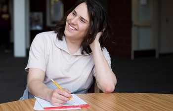 Student smiling at table with pencil and paper.