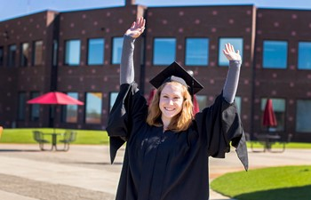 Student in cap and gown with arms in the air