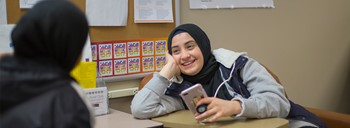 Student smiling with cell phone in Mosaic Center.
